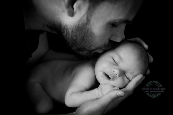 Dad kissing baby in newborn photoshoot