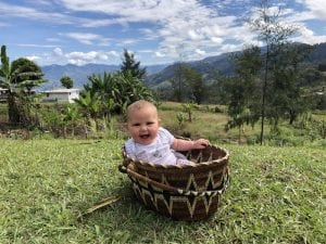 Baby in a basket with beautiful mountain views behind